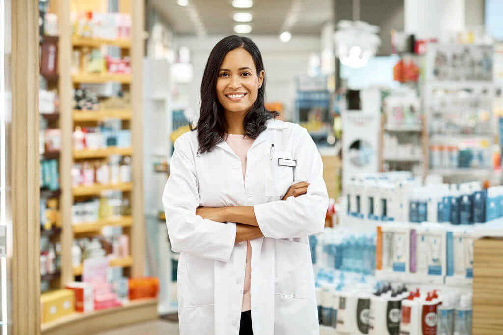 Young female pharmacist standing with arms crossed